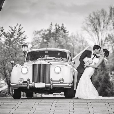 Bride and groom next to Rolls Royce Silver Cloud II limo